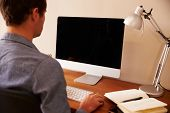 pic of telecommuting  - Man Sitting At Desk Working At Computer In Home Office - JPG