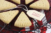 foto of shortbread  - Christmas shortbread triangle cookies on vintage baking rack on dark red rustic wood background with festive decorations - JPG