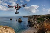 picture of drone  - A drone with raised landing gears and a camera flying in beautiful cloudy skies along spectacular sea cliffs with a calm ocean in the background - JPG