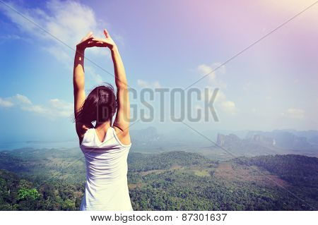 young woman stretching at mountain peak