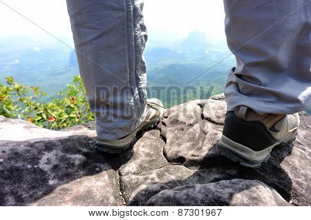 young woman hiker legs  at mountain peak rock