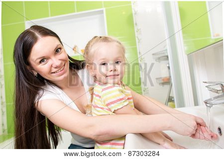 kid girl with mom washing in bathroom