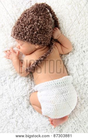 Newborn baby wearing a knitted hat and knitted diaper cover.