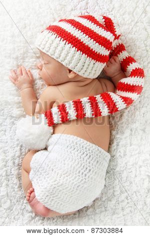 Newborn baby wearing a knitted Christmas elf hat.