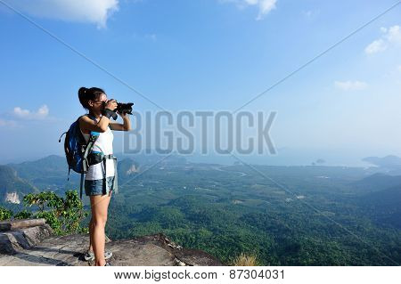 young woman photographer taking photo at mountain peak