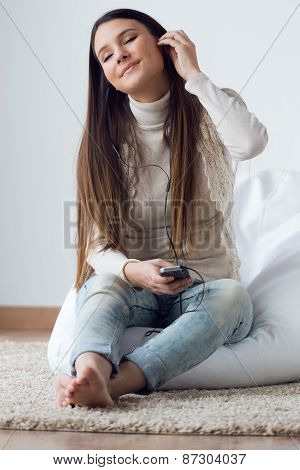 Beautiful Young Woman Listening To Music With Mobile Phone At Home.