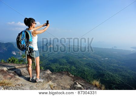 young woman hiker taking photo with smart phone at mountain peak
