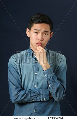 Pensive young Asian man looking at camera