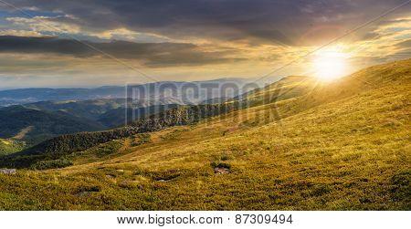 Valley On Hillside Of Mountain Range At Sunset