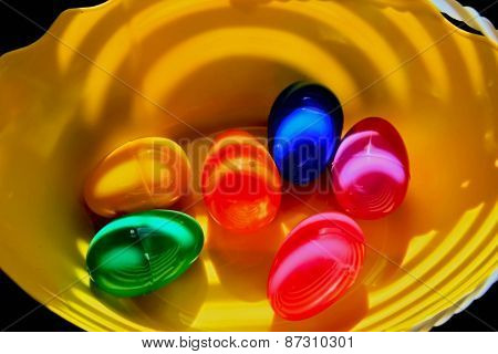 Colorful Easter eggs in a yellow sunlit bowl