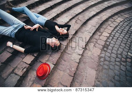 Boy and girl lying on the stairs and rest