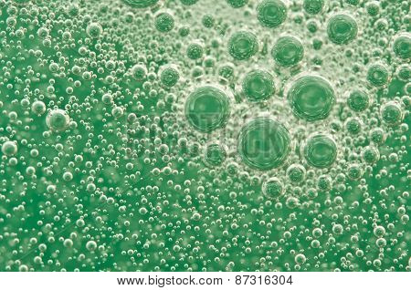 Macro Oxygen Bubbles In Water On A Green Background