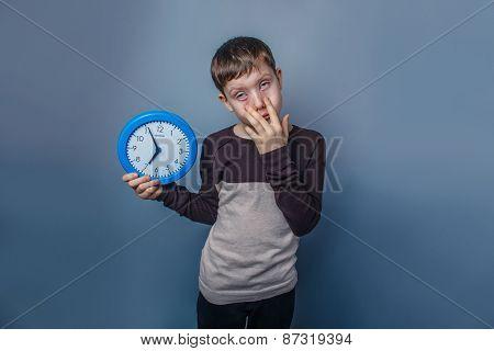 European-looking boy of ten years holding a wall clock rolled hi