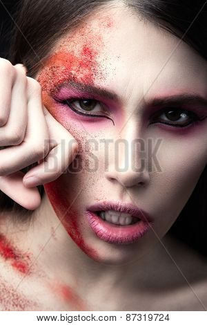 Portrait of a beautiful Girl with red paint on her face. Art beauty image.