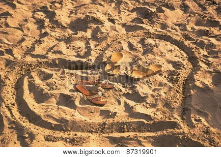 Heart Drawn On Sand With Bedroom-slippes Inside