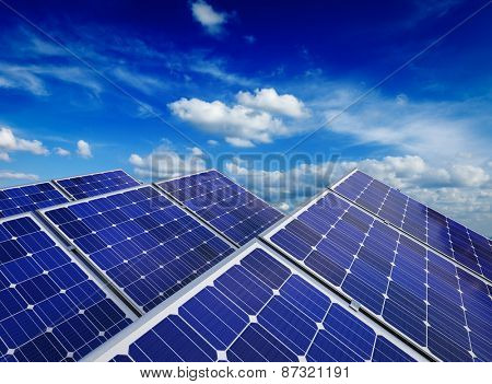 Solar power generation technology, alternative renewable energy and environment protection ecology concept  - close up of solar battery panels against blue sky with clouds