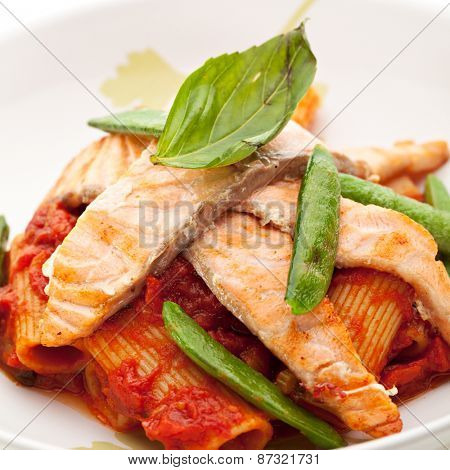 Pasta Penne with Fried Salmon. Garnished with Tomato Sauce
