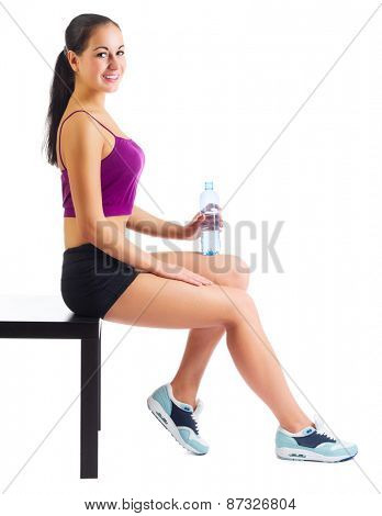 Sporty woman with water bottle sit on bench isolated