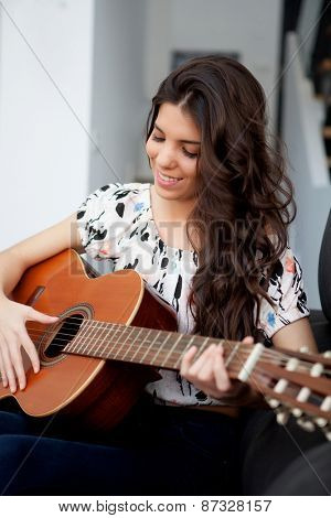 Young girl on the couch playing guitar