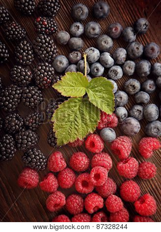 raspberries and blackberry blueberries scattered on the wooden table