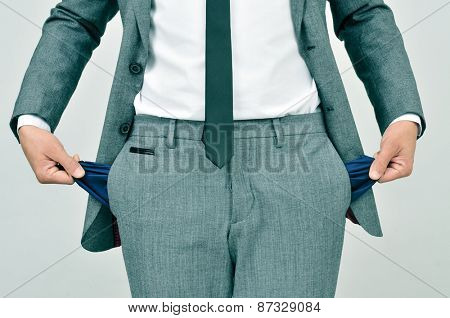 broke businessman wearing a gray suit showing his empty pockets