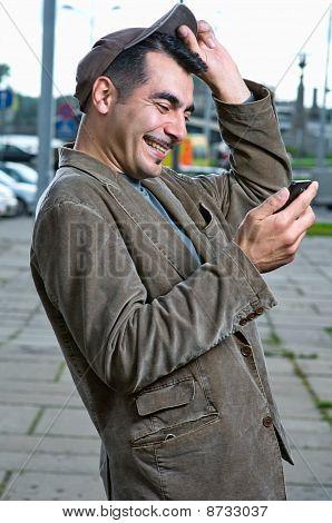 Feliz homem bonito com telefone móvel ao ar livre