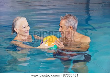 Happy senior couple playing water ball with beach ball in swimming pool