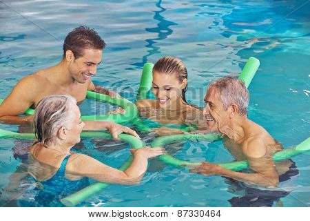 Happy family with senior couple in water of swimming pool