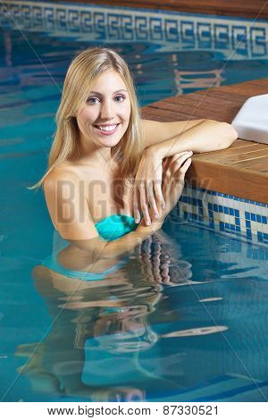 Smiling woman standing in water in swimming pool in a hotel