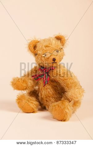 Stuffed vintage bear with glasses sitting on beige background