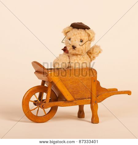 Hand made stuffed funny bear sitting in vintage wheel barrow