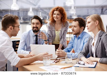 Several business partners looking at their colleague explaining viewpoint at meeting