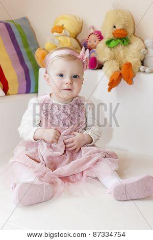 portrait of sitting toddler girl wearing pink dress