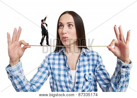 amazed woman looking at small man on the rope. isolated on white background