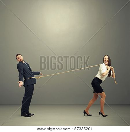 laughing woman lugging man in perplexity. photo on dark background