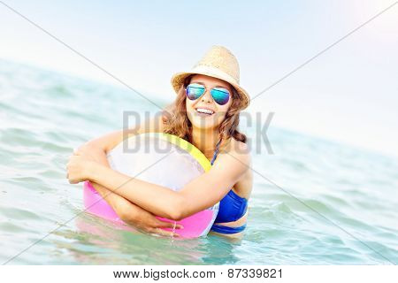 A picture of a young woman playing with a ball in the sea