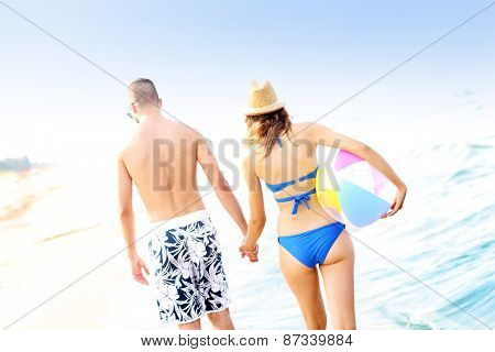 A back view of a young couple walking along the beach