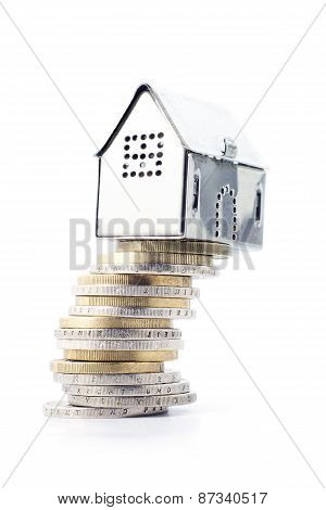 Risky Real Estate Investment, Small Silver House On A Slanted Stack Of Coins, Isolated On White