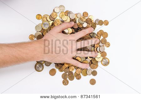 the male hand on a lot of gold coins. View from above