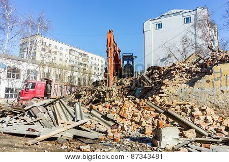Excavator loads garbage from demolished house