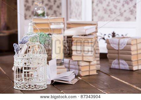 Cage With Birds And Old Book Heap In Interior Decoration