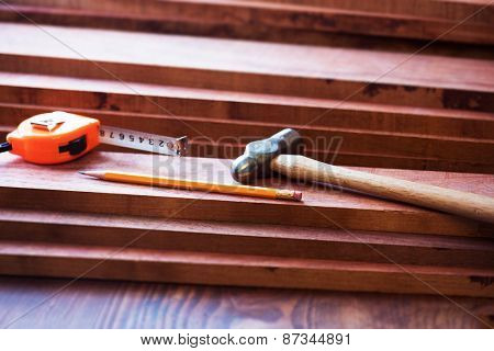 Interior wood working. FIne quality hardwood lumber, ready for use. pencil, measure, and a hammer on lumber.