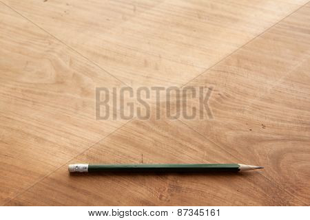 Pencil on a rustic wooden desk, in natural window lighting. Shallow depth of field. Focus is on the forehand pencil.