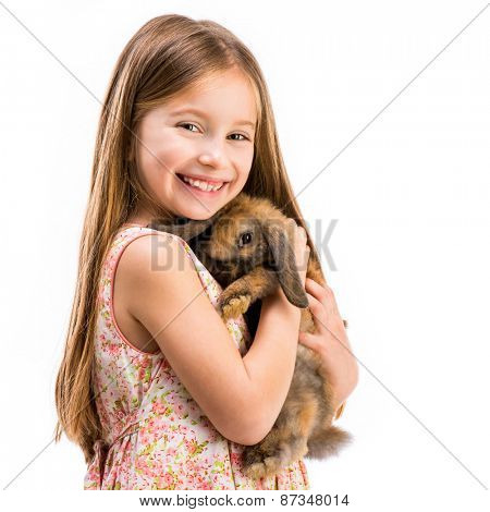 cute smiling girl in a summer dress with a baby rabbit close-up