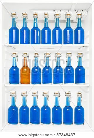 One orange Bottle among a large group of blue bottles in a fridge