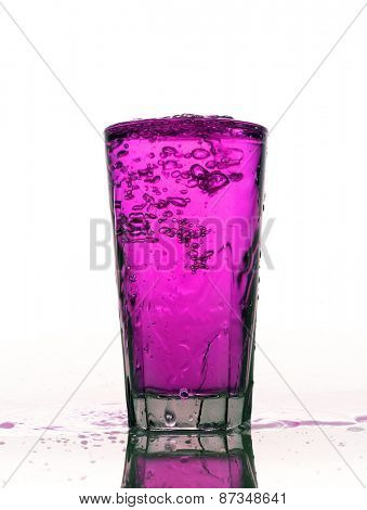 Glass of splashing Pink lemonade isolated on white background