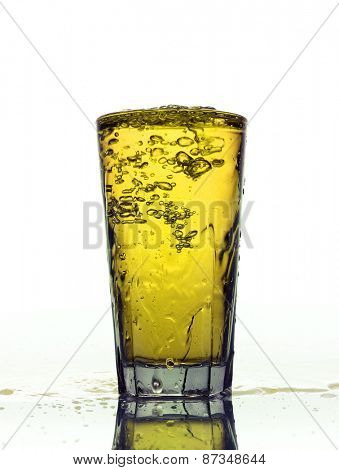Glass of splashing Yellow lemonade isolated on white background