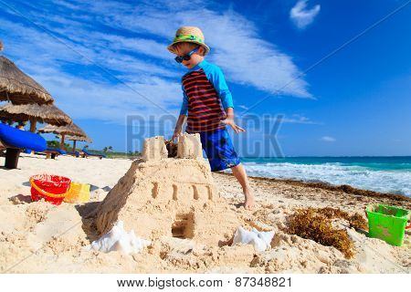 little boy building sandcastle on sand beach