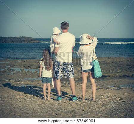Young family of four members in the summer on the beach. Back view
