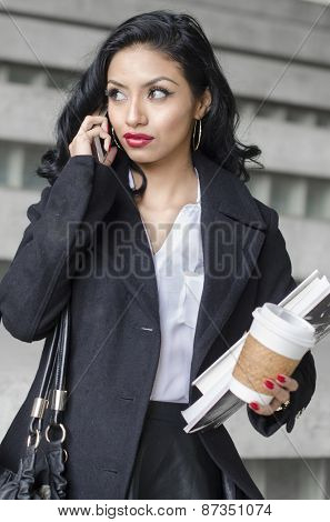 Active attractive young business woman, student, holding books and coffee while busy talking on phone